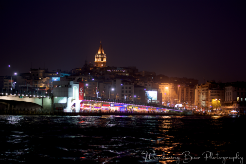 Galata Bridge illuminated by restaurants on the lower level and protected by Galata Tower in the distance.